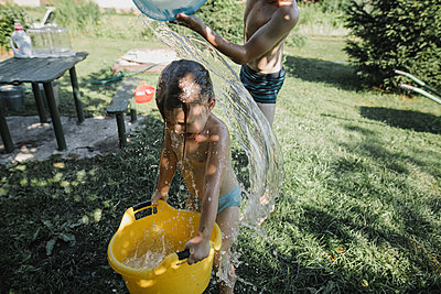 Brother and sister playing with water in garden - p300m2029567 by Katharina Mikhrin