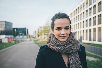 Portrait of smiling woman wearing scarf in autumn - p300m2070637 von Robijn Page