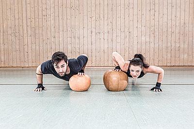 Man and woman practising with medicine balls in sports hall - p300m2144529 von Stefanie Baum