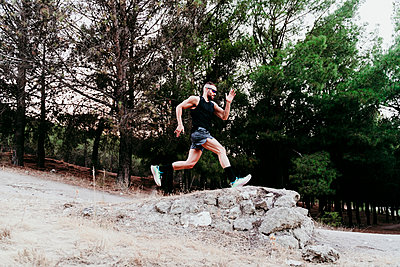 Male sportsperson running on rock against forest - p300m2251162 by Eva Blanco