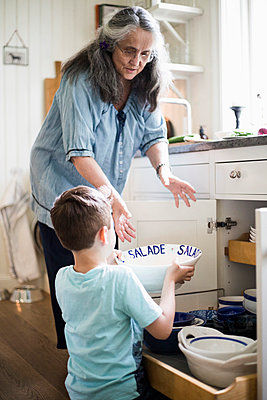 Boy giving utensil to grandmother in kitchen at home - p426m1507160 by Maskot