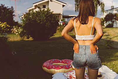 Junge Frau steht nachdenklich im Garten - p432m2230923 von mia takahara