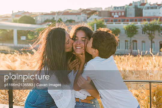 Young woman is kissed by her brother and mother. - p1166m2136583 by Cavan Images