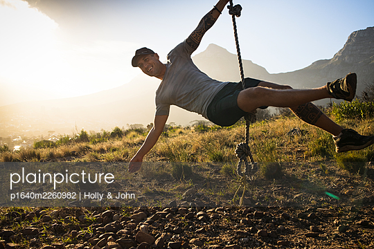Sporty man swings on rope at sunset - p1640m2260982 by Holly & John