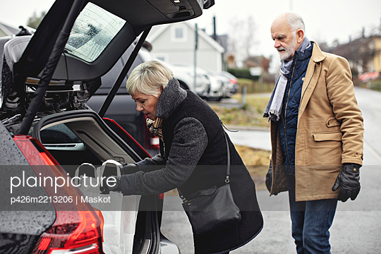 Senior man looking at partner standing by car trunk during winter - p426m2213206 by Maskot