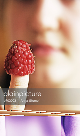 Young girl looking at raspberry - p7030031 by Anna Stumpf