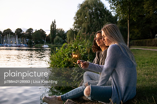 Two girlfriends with sparklers on the river bank - p788m2128993 by Lisa Krechting