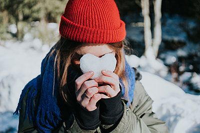 Young woman hiding face behind heart of snow - p1184m1424113 by brabanski