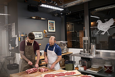 Male butchers cutting raw red meat in butcher - p1192m1493353 by Hero Images