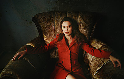 Fashionable woman wearing red coat an sitting on the vintage arm chair - p1577m2296855 by zhenikeyev