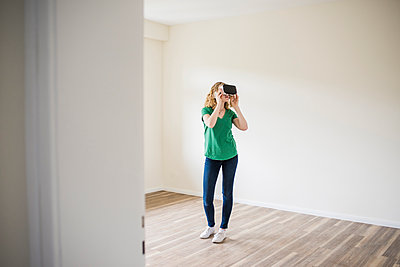 Woman in empty apartment wearing VR glasses - p300m1460528 by Uwe Umstätter