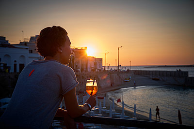Italy, Santa Maria al Bagno, woman relaxing with glass of Spritz at sunset - p300m1505562 by Dirk Kittelberger