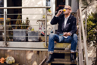 Senior man sitting on stairs of his patio, drinking coffee - p300m1588108 von Gustafsson