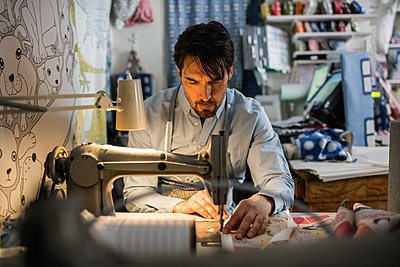 Serious male owner sewing fabric at shop - p426m1179383 by Maskot