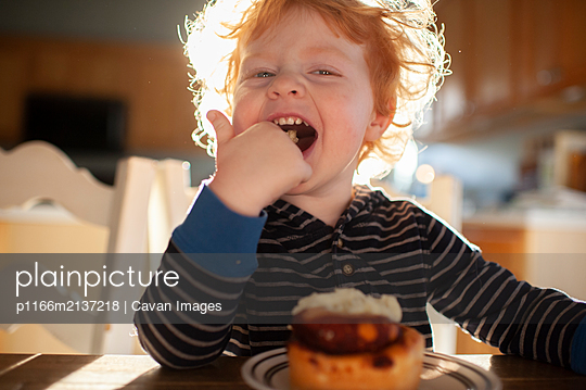 Toddler boy sitting at table licking frosting from finger at breakfast - p1166m2137218 by Cavan Images