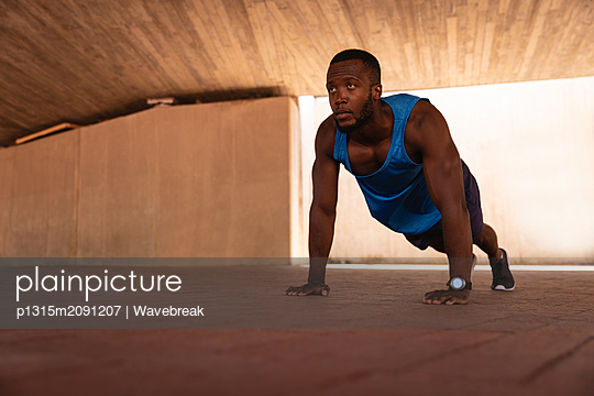 Man doing push-up exercise under the bridge  - p1315m2091207 by Wavebreak