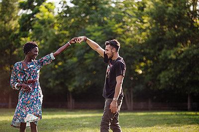 Happy couple dancing at park - p1166m1172823 by Cavan Images