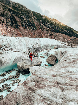 Young Female climber on crossing river on glacier Mer de Glace - p1166m2212340 by Cavan Images