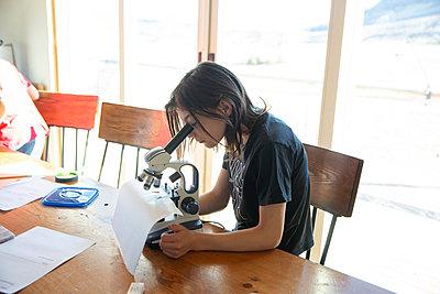 Girl homeschooling looking under microscope - p1166m2236936 by Cavan Images