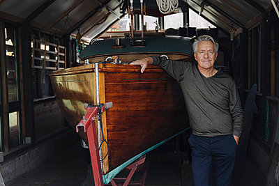 Portrait of a proud senior man at wooden boat in a boathouse - p300m2156251 by Gustafsson