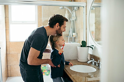 Side view of father watching daughter brushing teeth at sink in bathroom - p426m1451773 by Maskot