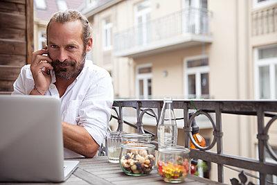 Man on balcony using smartphone - p788m1424666 by Lisa Krechting
