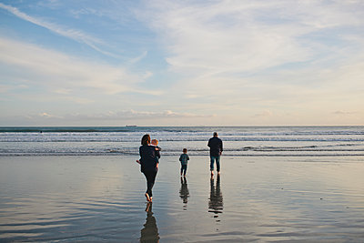 Rear view of family at beach against sky - p1166m1210259 by Cavan Images