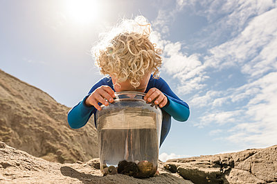 Curly haired child looking in bucket at a beach on a sunny day - p1166m2138187 by Cavan Images