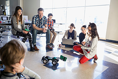Teachers and pre-adolescent students programming robotics in classroom - p1192m1231028 by Hero Images