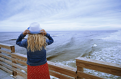 Woman on a wooden pier looking to the ocean - p1577m2150323 by zhenikeyev
