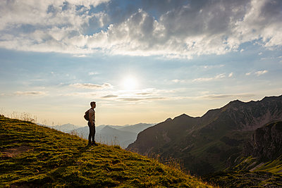 Germany, Bavaria, Oberstdorf, man on a hike in the mountains looking at view at sunset - p300m2028801 by Daniel Ingold