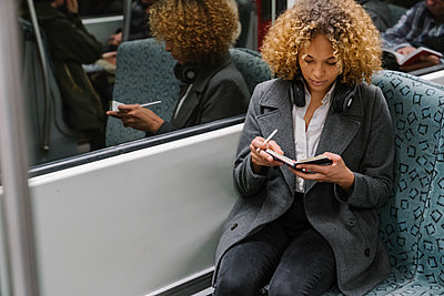 Woman taking notes on a subway - p300m2143451 by Hernandez and Sorokina
