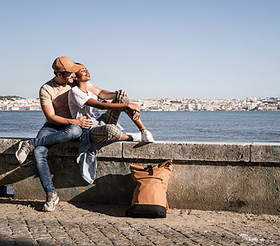 Young couple sitting on a wall at the waterfront, Lisbon, Portugal - p300m2144506 by Uwe Umstätter