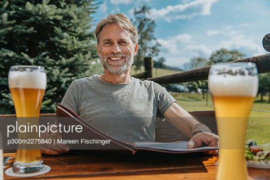 Smiling bearded man holding menu while sitting in beer garden - p300m2275840 by Mareen Fischinger