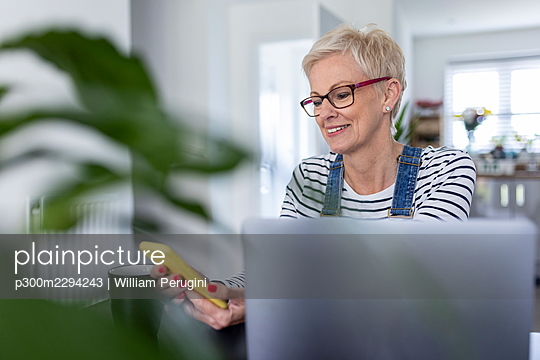 Smiling mature businesswoman using smart phone at home office - p300m2294243 by William Perugini