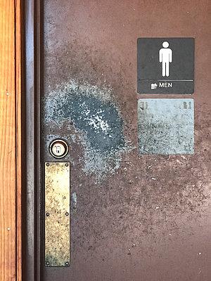 Well worn Men toilet door - p1048m2025629 by Mark Wagner