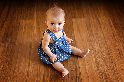 High angle portrait of baby girl sitting on floor at home - p1166m1403777 by Cavan Images