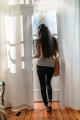 Rear view of a young woman standing at the window at home with a guitar - p300m2132363 by Richárd Bellevue