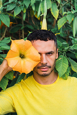 Portrait of man with blossom of angel's trumpet - p300m2155112 by VITTA GALLERY
