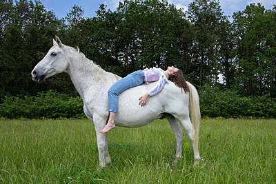 Young woman lying on back of a horse - p300m2155779 by Petra Stockhausen