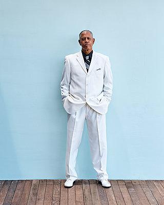 Portrait of senior businessman, blue background - p429m2145766 by Aaron Fallon