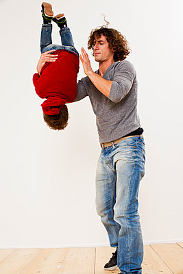 Studio shot of father turning over son in mid air - p429m895463f by Emely