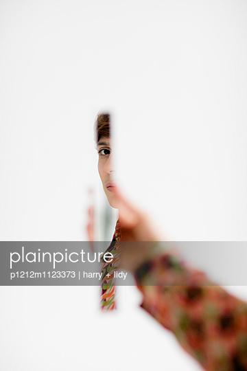 Frau mit einem Stück Spiegel in der Hand - p1212m1123373 von harry + lidy