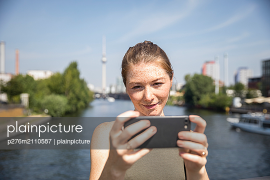 Young woman takes selfie at the river Spree - p276m2110587 by plainpicture