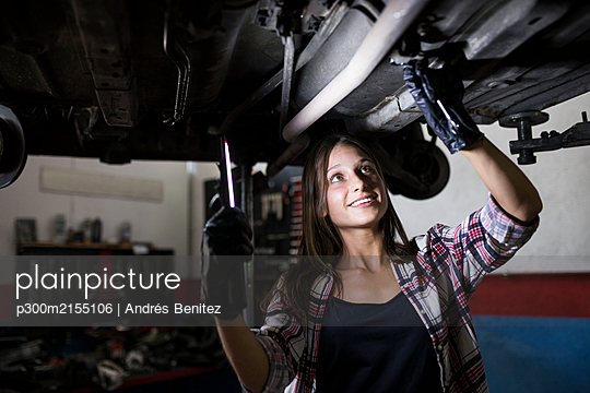 Smiling woman with lamp fixing car standing under bottom in car repair service - p300m2155106 by Andrés Benitez