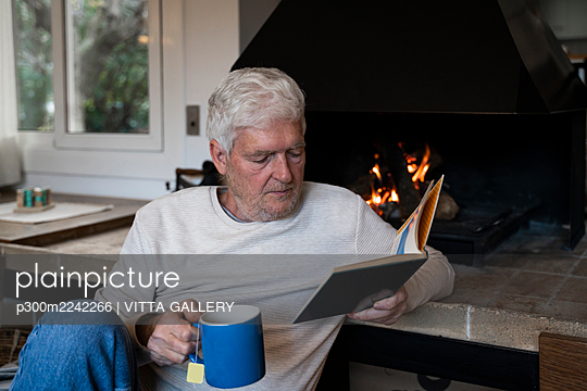 Senior man with coffee cup reading book while sitting by fireplace at home - p300m2242266 by VITTA GALLERY