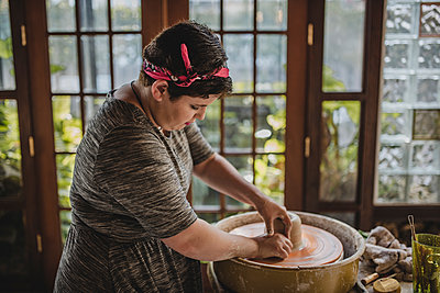 Potter using pottery wheel to make clay pot at workshop - p1166m1512991 by Cavan Images