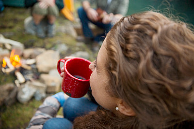Woman drinking coffee at campfire - p1192m1184083 by Hero Images