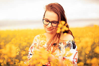 Smiling young woman in a rape field - p300m2277600 by Sebastian Dorn