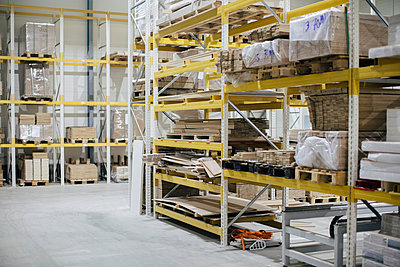 Stack of wooden planks on racks in distribution house - p426m1537062 by Maskot